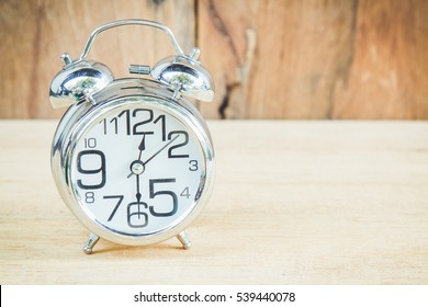 Clock show 12 am or pm and 30 minute on wood background with copy space.
