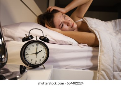 clock show 2 O'clock and woman sleepless on the bed