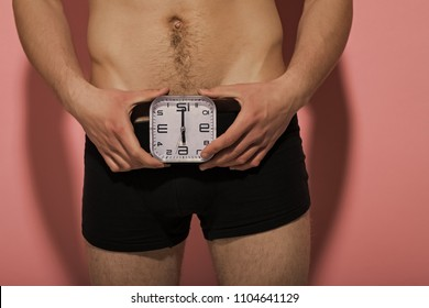 Clock show six oclock at male underwear on pink background. Health, strength, power. Potency, desire concept.