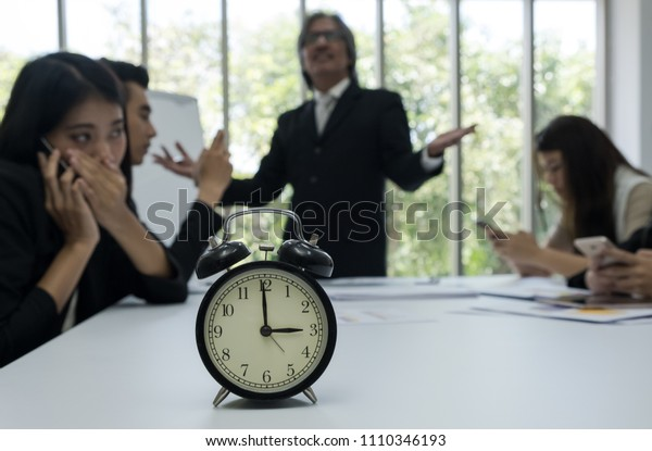 Clock show time,with senior manager bored with new generation of employees who not interested in meeting blur background.