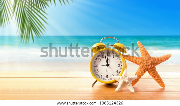 Clock showing nearly 12 on the tropical beach