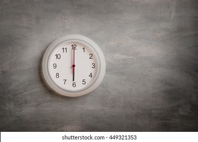 Clock showing six o clock on gray wall