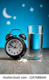 Clock, sleeping pills and glass of water on wooden table under night sky. Treatment for insomnia, sleeplessness.