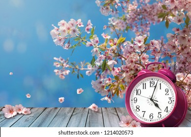 Clock and spring cherry flowers on wooden table - daylight saving time concept