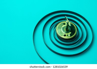 Clock spring with gear on a blue background, metal spiral