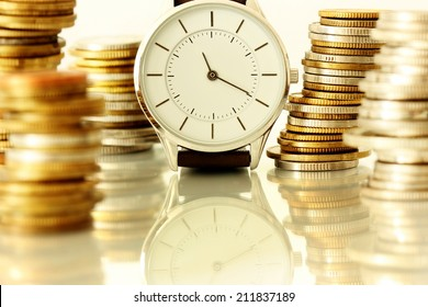 clock and stacks of coins : time - money