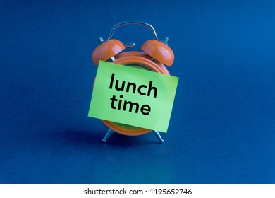 Clock, sticky note and words Lunch Time on dark background with selective focus