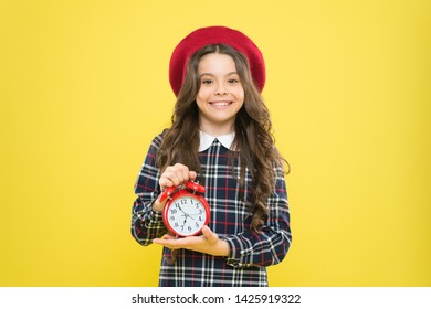 Clock is ticking. Small child smiling with mechanical clock on yellow background. Adorable kid with long brunette hair and wakeup clock. Happy little girl holding alarm clock.