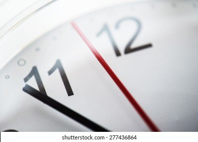 Clock or time abstract background. white clock with red and black needles. Focus is on red Around the mid point of the red needle. Intentionally shot with extremely shallow depth of field.