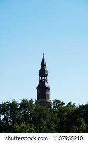 clock tower above treetops and clear sky background with copy space, church of the new town in Hannover Germany