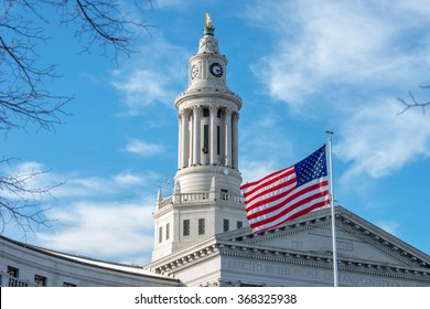 Clock Tower of Denver City Hall - A close-up view of the clock tower, topped with a golden eagle, of Denver City and County Building, with a US flag flying at front. Denver, Colorado, USA.