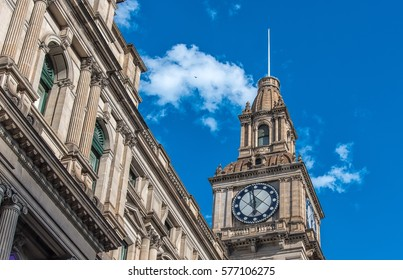 The clock tower of the Melbourne GPO building against a blue sky, light cloud cover and a single bird flying above