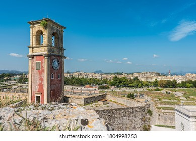 Clock tower at the old fortress at Corfu city with the esplanade and the old town on the background. Greece 2020.