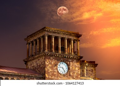 Clock tower on the government building on Republic Square in Yerevan. Armenia, Beautiful sunset with moon in the background. Toned