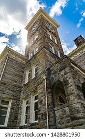 Clock tower on old stone building, windows, blue sky, clouds and sunlight burst