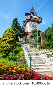The clock tower (the Uhrturm) and bell tower (the Glockenturm) and flower garden in the city of Graz in Austria. Bright colors and blue sky
