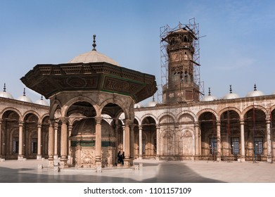 A clock tower under construction and a ablution fountain with group of people in a courtyard of the Great Mosque of Muhammad Ali Pasha (Alabaster Mosque) in the Citadel of Cairo in Egypt.