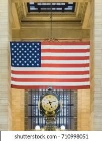 Clock and USA flag at Grand Central Terminal - Manhattan, New York, NY, USA