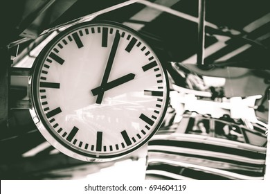 Clock or watch attach the pole under the roof, Beautiful big white clock or watch with line numbers is hanging under the roof of train station in black and white tone