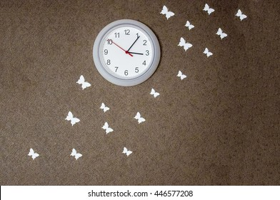 Clock and white butterflies on the wall.