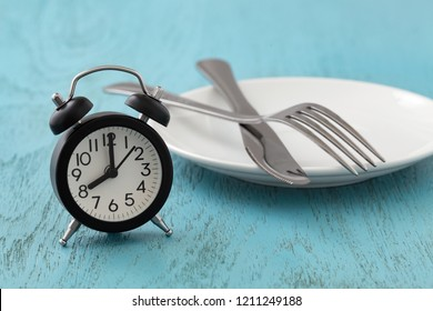 Clock with white plate, fork and knife, intermittent fasting, diet, weight loss concept on blue wooden table
