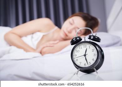 clock with woman sleeping on the bed
