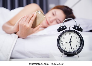 clock with woman using her smartphone on bed in the bedroom