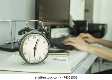 clock and working hand with a computer