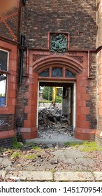 Clockface, St Helens, Merseyside. UK. 07/15/2019 The Green Dragon public house as its being demolished. A view of the front door with rubble on the floor and an excavator arm viable through the door.