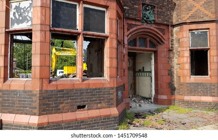 Clockface, St Helens, Merseyside. UK. 07/15/2019 The Green Dragon public house as its being demolished.  A view of the front with part of an excavator viable through the window.