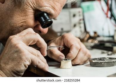 Clockmaker repairing wrist watch.