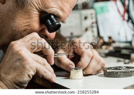 Clockmaker repairing wrist watch.