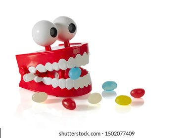 Clockwork jaw toy with a blue Lollipop in its teeth and scattered randomly colored candies isolated on a white background with shadows. Free space for your text.