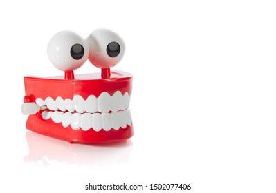 Clockwork jaw toy isolated on white background. Black humor, horror.