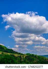 Clods in an almost perfect row in the blue sky over hilly landscape