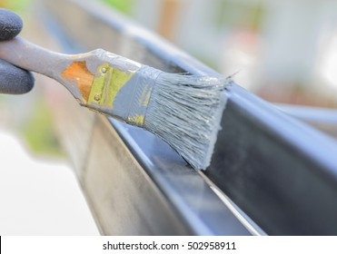 Cloes up hand with paintbrush painting a steel.