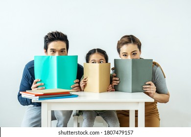 Cloesup portrait of adorable attractive beautiful asian family, Asian young mother and father with little daughter sit at desk and holding book with funny facial expression