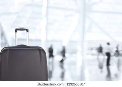 Cloeup of a suitcase with blurred travellers in Airport or Railway Station.