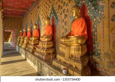 Cloister with gilded Buddha images, Wat Arun Rajwararam Thonburi, Bangkok, Thailand.
