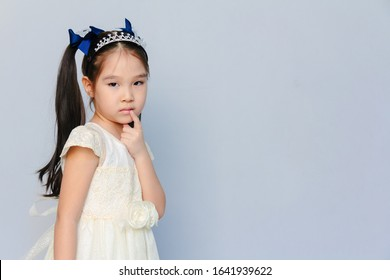 Clope-up portrait of a cute 6 years old Asian girl thinking