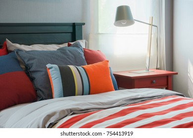 Clorful pillows on bed with red striped blanket in modern interior bedroom
