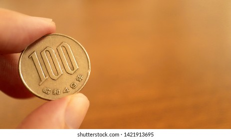 Close up the 100 Japanese Yen Coin on Finger