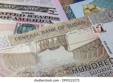 Close up to 100 Sudanese pounds of the Republic Sudan beside US dollars banknotes. 100 Pound banknotes of the African country Sudan. Money US with sudanese banknote. World currency. Hundred Pound