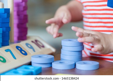 Close up 2 years baby boy hands.Little child boy playing with lots of wooden toys block with mother.Kids play with educational toys at home.Day care and Kindergarten school.child development concept.