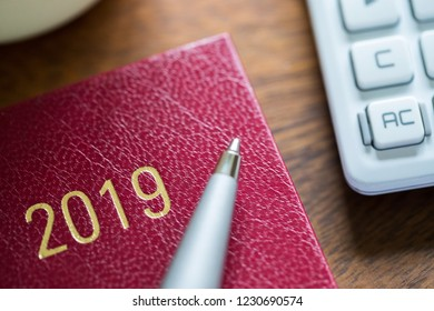 Close Up Of 2019 Diary With Pen And Calculator On Wooden Desk