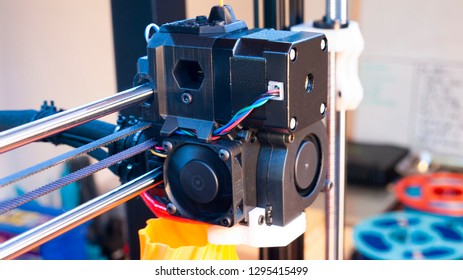 Close up of a 3D printer extruder and the parts and wiring of it while it is printing an orange vase.
