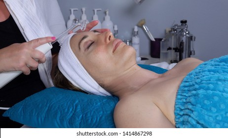 Close up of a 40 year old woman receiving high frequency facial treatment in a spa