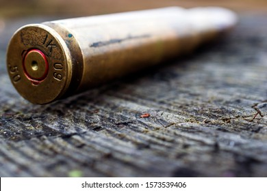 close up of 50 mm bullet on wooden background