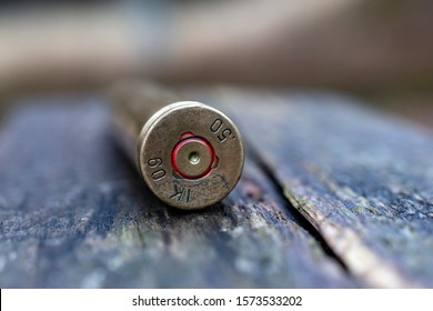 close up of 50 mm caliber bullet on wooden background