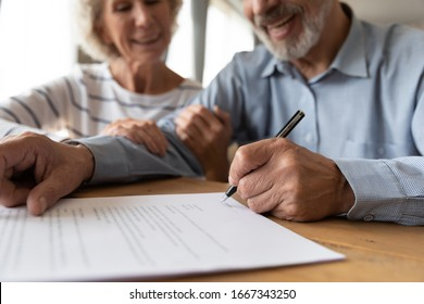 Close up of 60s husband and wife sit at desk sign health insurance contract close deal, smiling old mature couple spouses put signature on document make good agreement, elderly healthcare concept